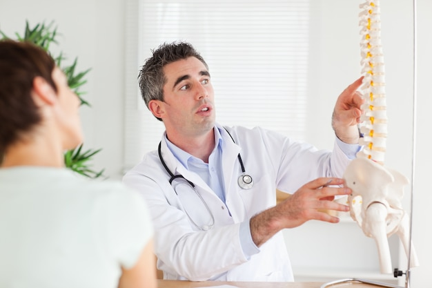 Doctor showing a woman a part of a spine