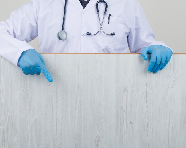 Доктор показывает деревянную доску в белом пальто и перчатках