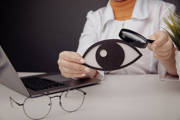 Doctor showing a wooden eye by magnifier. healthcare concept.