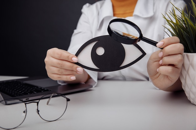 Doctor showing a wooden eye by magnifier