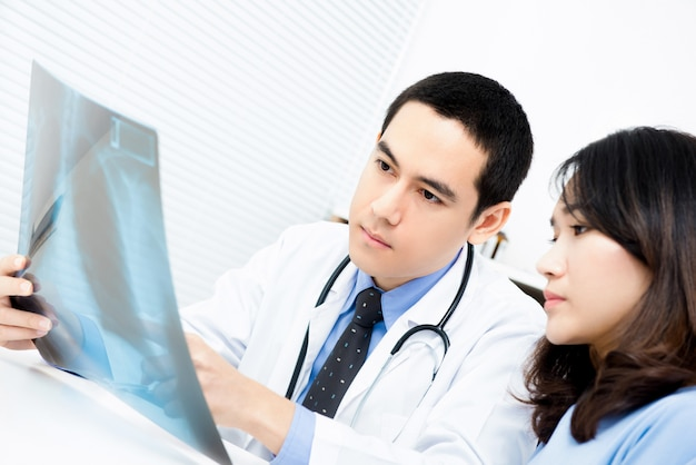 Doctor showing x-ray image to female patient