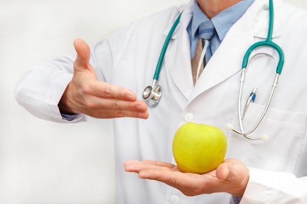 의사는 건강한 식단을 위해 사과를 보여줍니다
