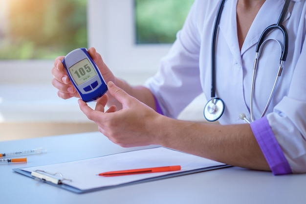 Doctor shows glucose meter with blood glucose level to diabetes patient during medical consultation and examination in hospital. diabetic lifestyle and healthcare