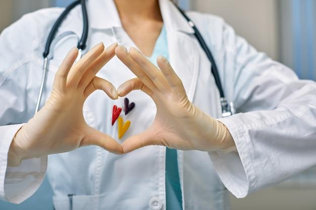 의사는 의료 개념, 병원 의학, 심장학으로 심장의 모양에 접힌 손을 통해 심장의 simbols를 보여줍니다.