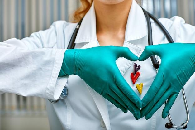 의사는 의료 개념, 병원의 의학, 심장학을 가진 심장 모양으로 접힌 손을 통해 심장의 simbols를 보여줍니다