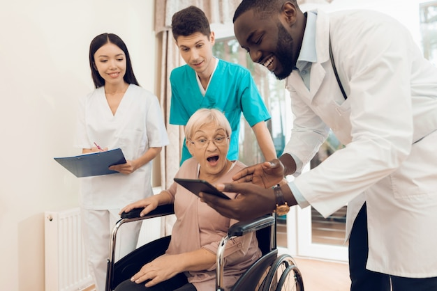 Doctor shows something on the tablet to an elderly patient.