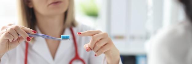 Врач показывает зубную щетку пациенту. выбор правильной концепции зубной щетки