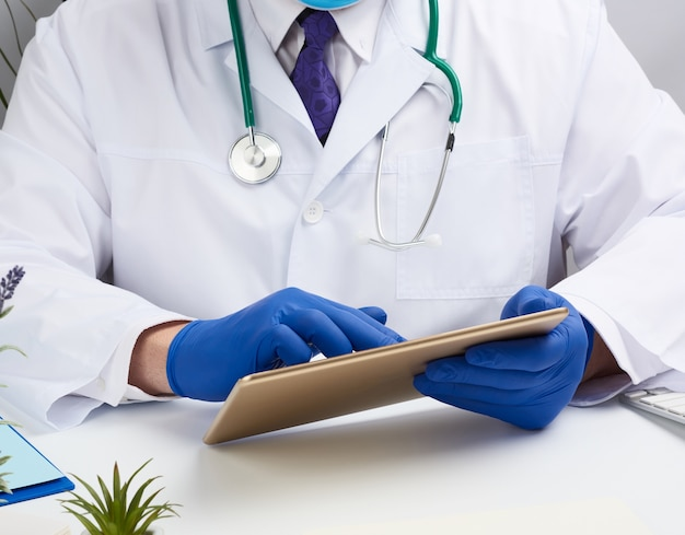 Доктор сидит за столом и держит электронный планшет