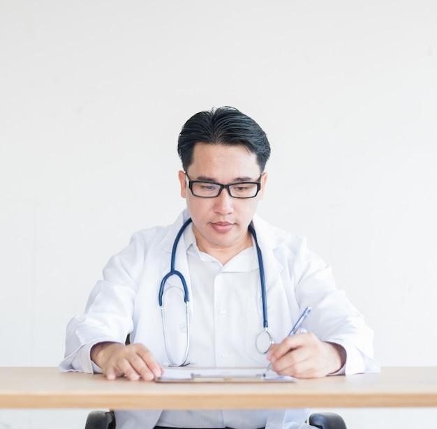 의사는 종이와 의사의 사무실에 앉아입니다.