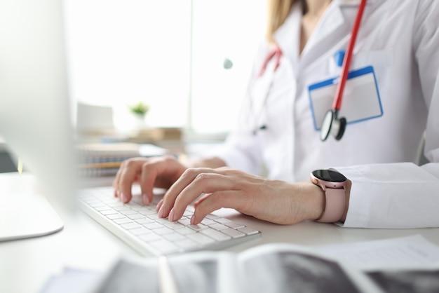 의사 테이블에 앉아 컴퓨터 키보드 근접 촬영에 입력