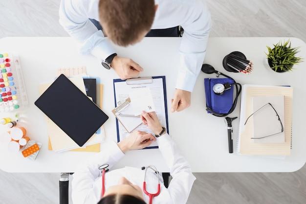 의사는 테이블에 앉아 환자의 상위 뷰 의료 개념에 처방전을 작성합니다.