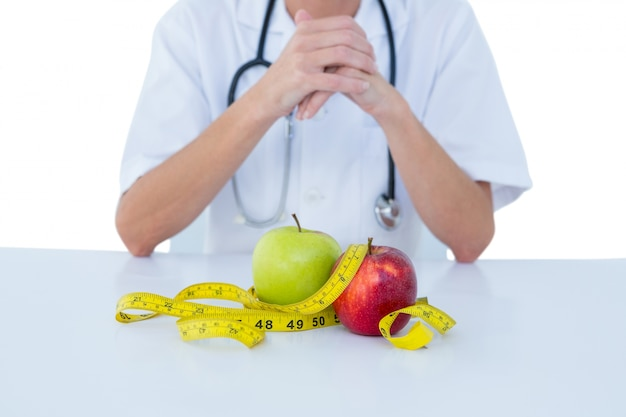緑と赤のリンゴで机の後ろに座っている医者