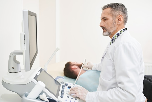 Doctor sitting, looking at screen, doing diagnosis of neck.