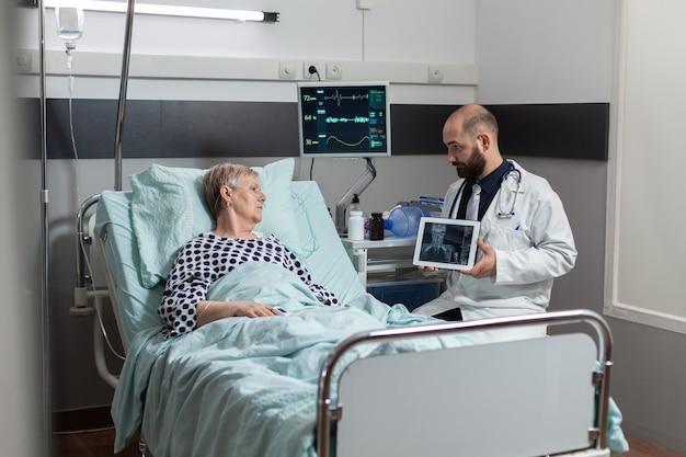 体の外傷の診断を説明する年配の男性の隣に座っている医師