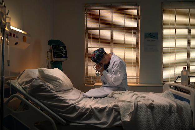 悲しい間病院のベッドに座っている医者