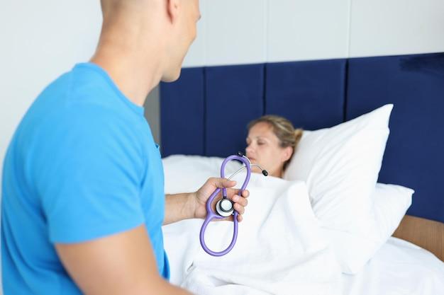 의사는 환자 침대에 앉아서 손에 청진기를 들고 병원 치료 개념