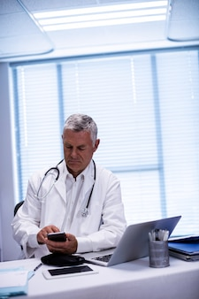 Doctor sitting at tablet and using mobile phone