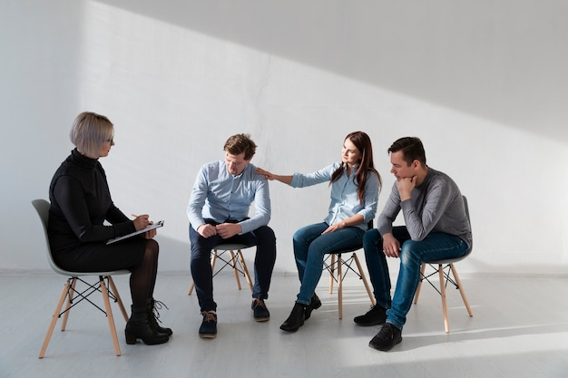 Doctor sitting with rehab patients in a white room