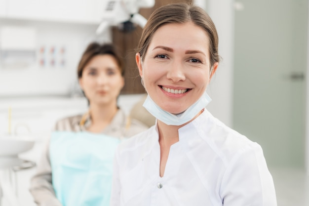 Doctor smiling at the camera, with her patient waiting to be checked up in the background