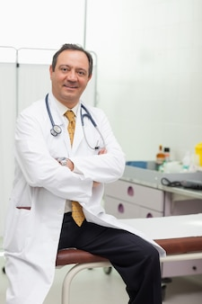 Doctor smiling while sitting on a table