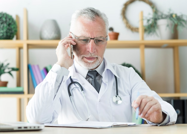 Doctor speaking on phone in office
