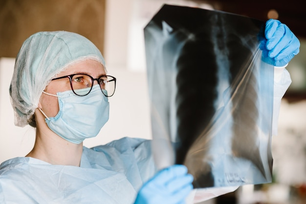 Doctor specialist pulmonary medicine holding radiological, chest x-ray film for medical diagnosis on patient health on infected coronavirus, covid-19, asthma, lung disease and bone cancer illness.