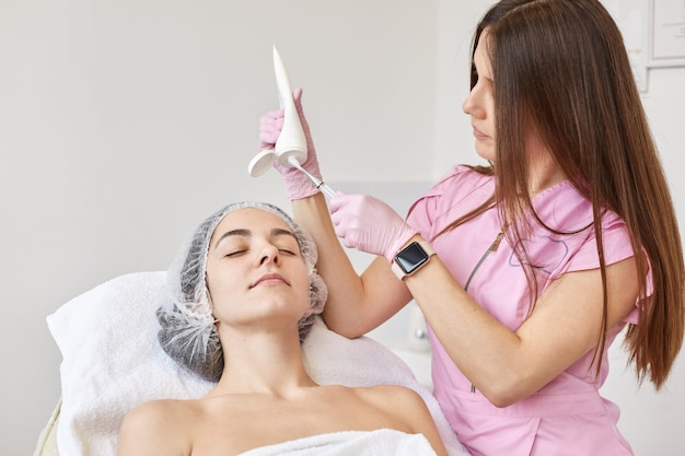 Доктор выдавливает косметологическое средство из флакона, готовит процедуру увлажнения. женщина в салоне красоты