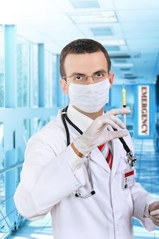 의사는 병원에서 약이 든 의료 주사기를 들고 서 있습니다.