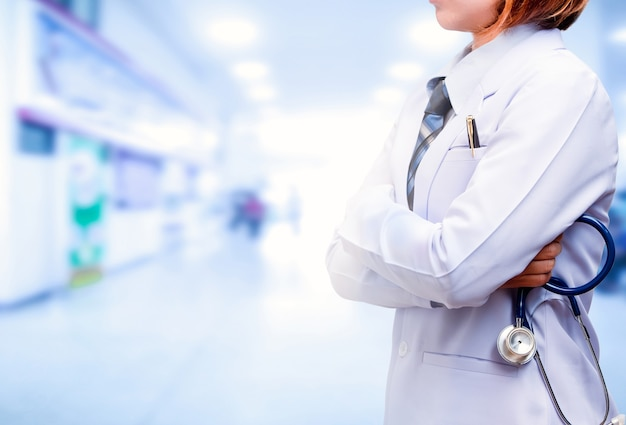 病院の背景がぼやけた青い聴診器を持って立って腕を組んだ医師