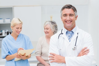 Doctor standing arms crossed with nurse and patient in background