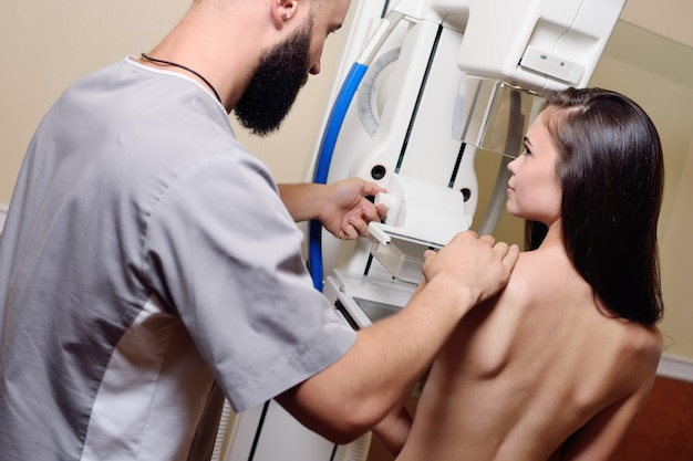Doctor standing assisting patient undergoing mammogram x-ray tes. prevention of breast cancer