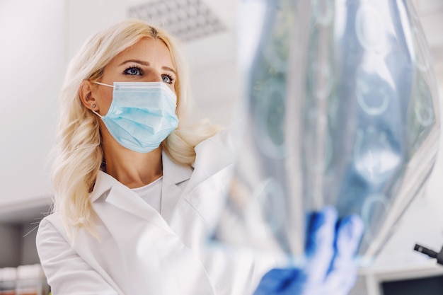Врач стоит в больнице с маской и резиновыми перчатками и смотрит на рентгеновский снимок мозга пациента