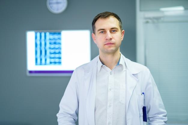 Доктор, стоя в офисе с рентгеновским снимком на заднем плане.