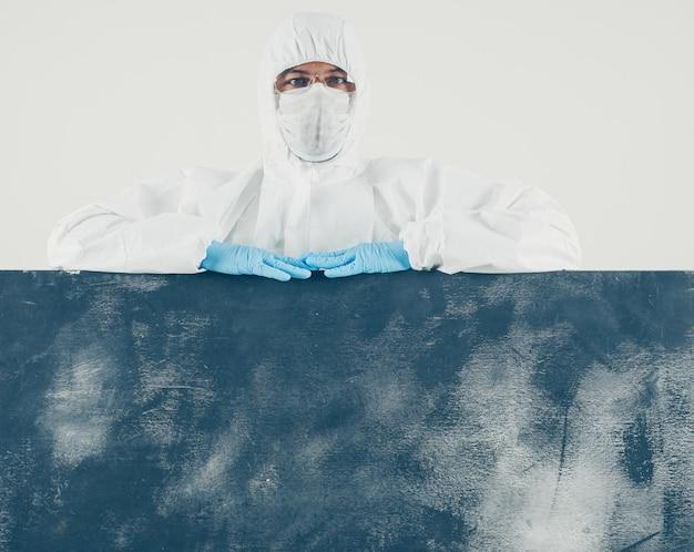 Un medico in piedi e guardando in bianco e bordo scuro in maschera, guanti e tuta protettiva