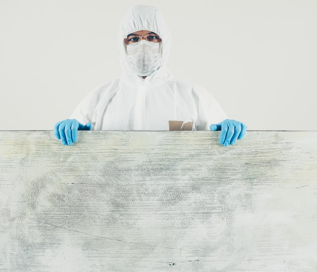 A doctor standing in white and wooden board in mask, gloves and protective suit