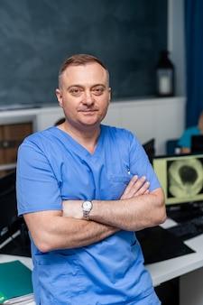Doctor stands cross hands. blue scrubs. medical office background. medical worker.