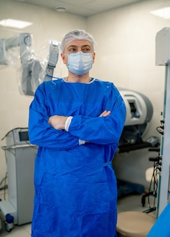 Доктор стоит скрестив руки. медицинское роботизированное устройство на заднем плане. минимально инвазивные хирургические инновации, хирургия медицинского робота с эндоскопией.