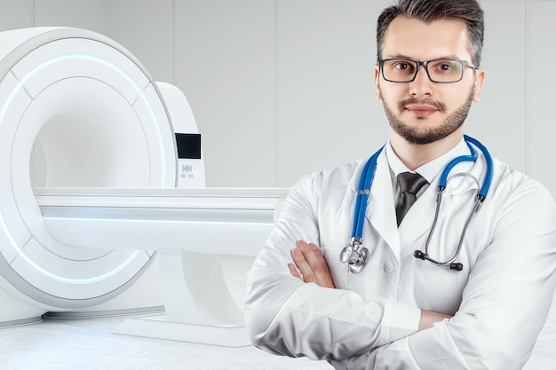 The doctor stands in front of the mri machine.