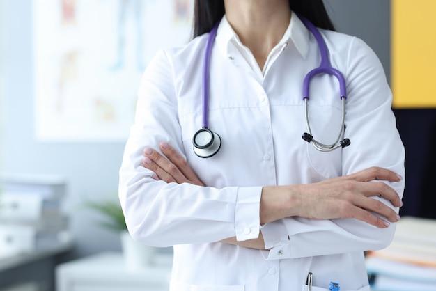 医者は診療所で胸に腕を組んで立っています。医者の職業についてのすべて