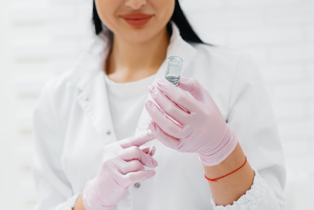 A doctor stands with a syringe before an intramuscular injection to treat the virus.