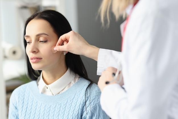 医師が患者の顔に絆創膏を貼り付ける