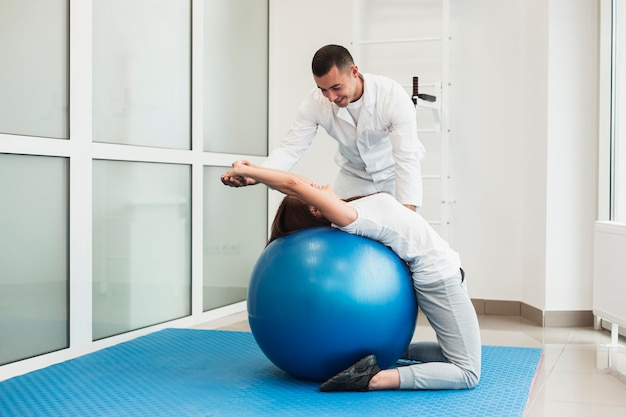 Doctor stretching patient on exercise ball