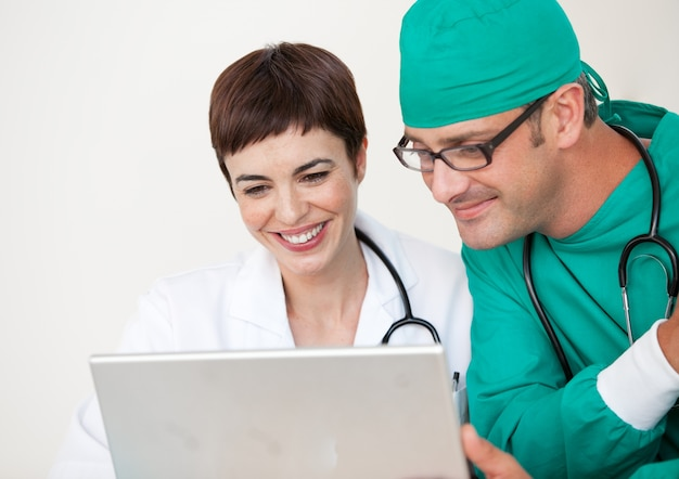 Doctor and surgeon looking at a laptop