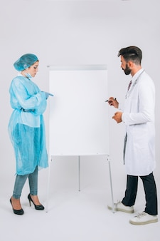 Doctor and surgeon at presentation with whiteboard