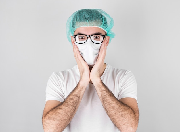 Doctor surgeon in white medical mask and a medical cap stands over white background with surprise,holding face with the hands. ð¡oncept of covid 19, flu and seasonal cold.