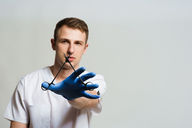 Doctor surgeon with needle holder in medical gloves on white surface