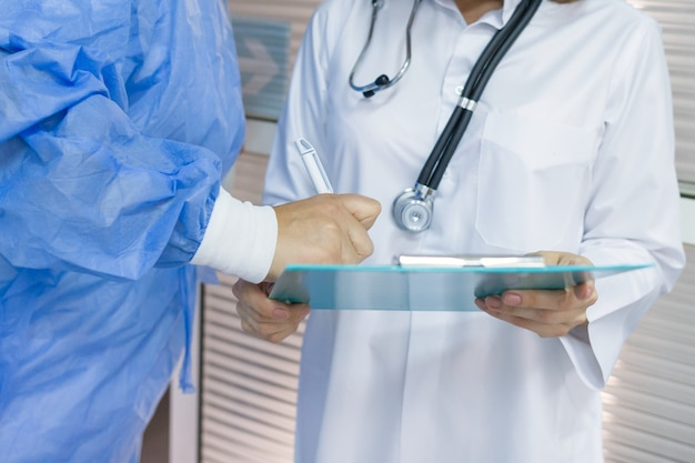 Doctor surgeon writes medical document on clipboard