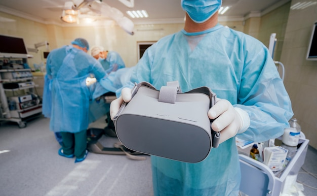 Doctor in a surgical room with virtual reality glasses on the background of the real operation.