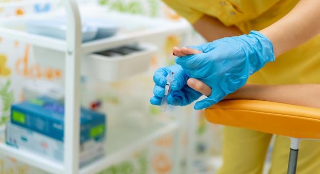 医者は子供の指から血を取ります。医療チューブに血が落ちる。クリニックの研究室。
