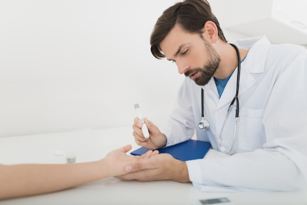Doctor takes a blood sample from boy to check it for sugar.
